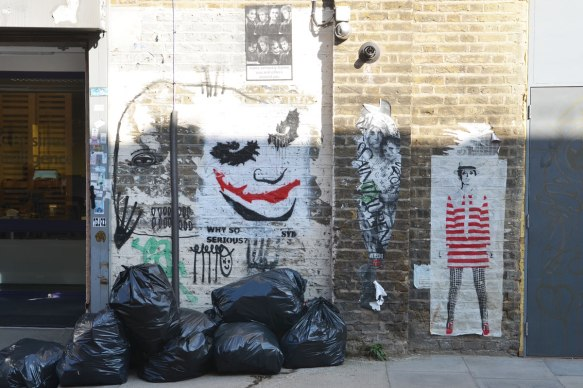 a wall in Fashion street, London E1, with a painting of the jokers face and some paste ups