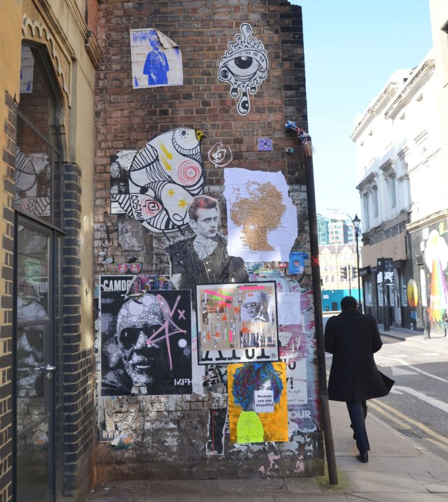a man walks past a wall that is covered with stickers and paste ups graffiti and street art in Shoreditch London