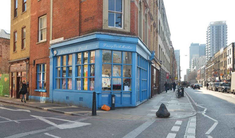A storefront in a line of brick buildings, at an intersection, with blue wood window frames and door frame, a woman is walking past. the store is called, L and L, Fairy Goth Mother