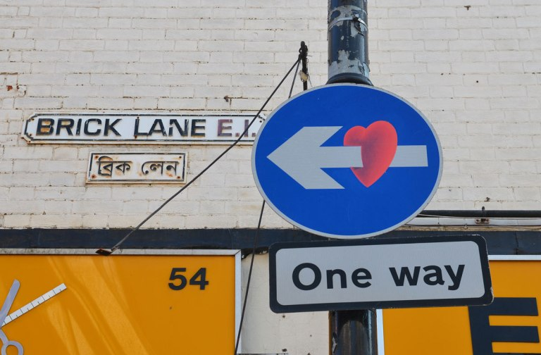 one way sign, blue circle with an arrow pointing left, a heart has been added to make the arrow look like it has pierced the heart