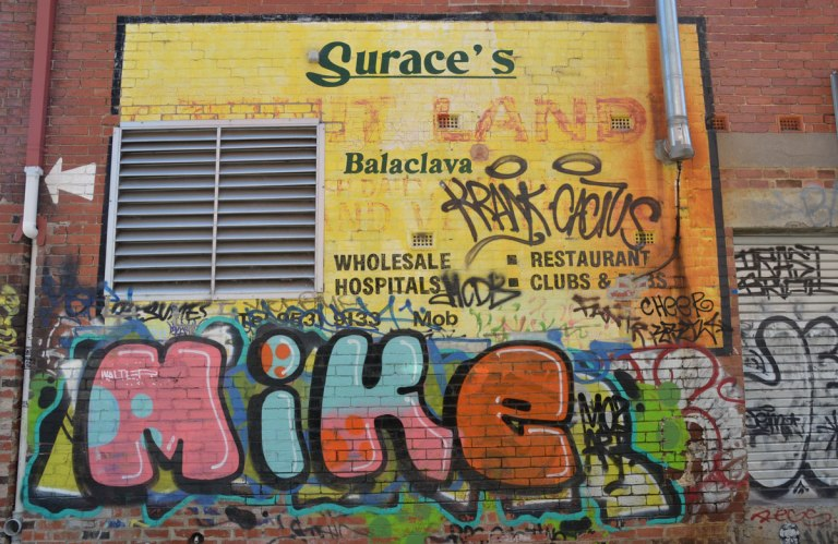 on the side of Surace's store in Balaclava Melbourne, a large graffiti text of the name Mike in fat letters