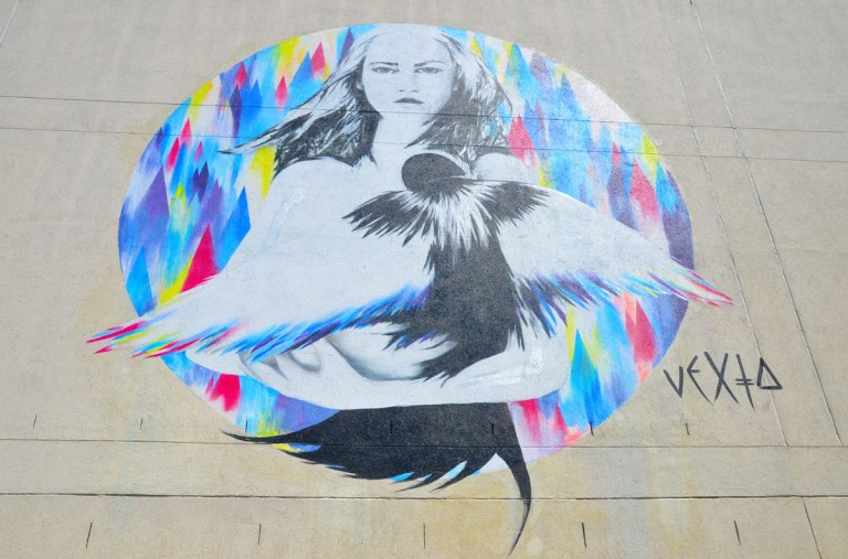 a street art painting of a woman in a multicoloured background circle