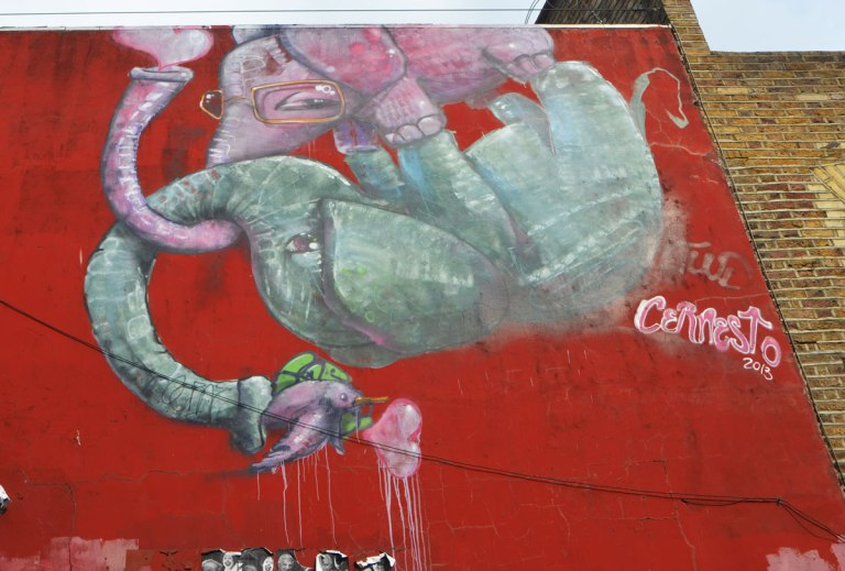 an upside down elephant painted on a wall by cannesto, with a pink elephant entangled with it.
