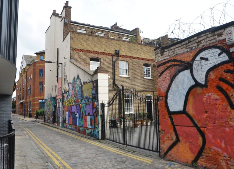 looking up a street, Chilton St., two buildings and a fence with a lot of street art on them.