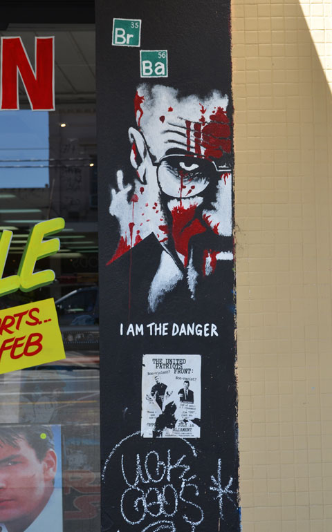 one side of man's face in black and white with red splotches in it, under the face are the words I am the Danger.