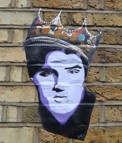 a paste up head of Elvis with a gold & jewel crown on his head