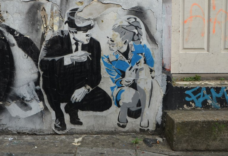 a paste up of a man and a woman squatting on one knee beside the front step of a door. They look like theyare talking to each other.