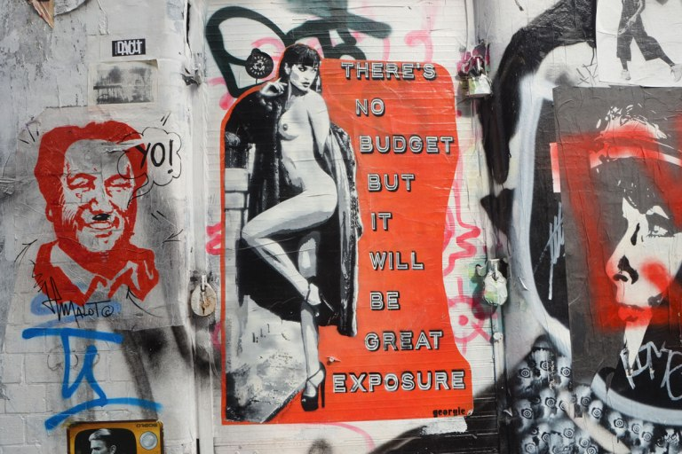 a wall of graffiti and street ast, the central piece is a nude woman, one knee bent up to cover herself, with large words on bright red background beside her that say There's no budget but it be great exposure.