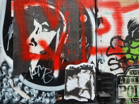 graffiti stencils and paste ups on a wall, a woman's head in profile, a couple kissing, red spray scrawls