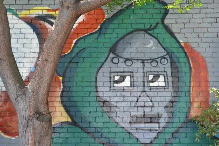 a tree trunk is in front of a mural that features a grey face encircled by a green hoodie