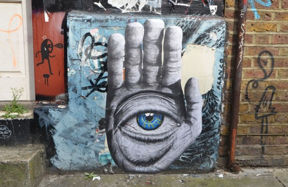 street art, paste up of a very large hand, palm facing frontwards with a large very realistic looking blue eye in the center of the palm.