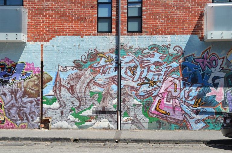 large abstract and text street art on a brick wall, pale blue background