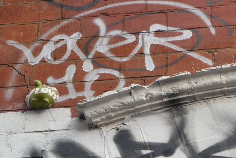 a tiny green 3D animal graffiti stuck on a wall up fairly high, with the word love painted on it in white