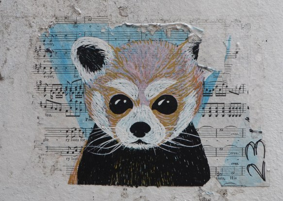 street art pasteup of the head of a little furry animal, painted on a piece of sheet music