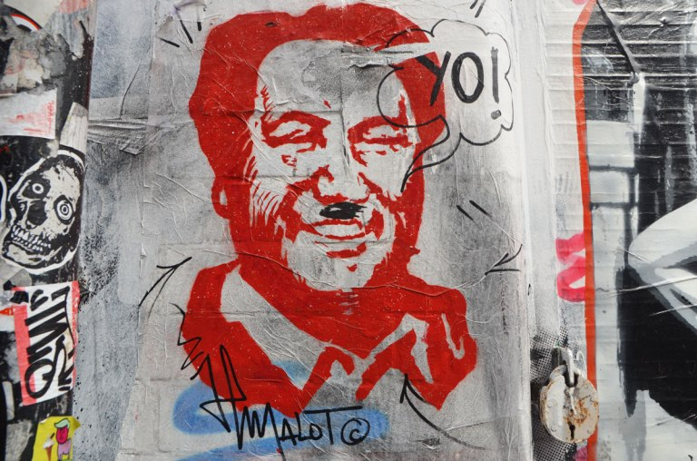 a man's head, stencil in red, someone else has given him a black Hitler moustache and a word bubble that says yo! Signed malot.