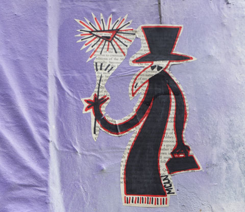 Spy guy figure in long black coat, black tophat and carry black bag. In other hand has a stick that is either a light or a magic wand. Triangular object above the stick. Signature is mcln. drawn on old book page, and pasted on a purple wall, outdoors.