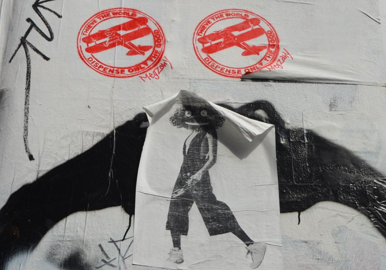 two red stencils of biplanes, with a paste up of a person's body, white sneakers on feet, but with muppet head.