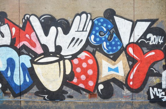 a mural featuring parts of Mickey Mouse and Minnie Mouse including a white glove, part of a bow, a bowtie