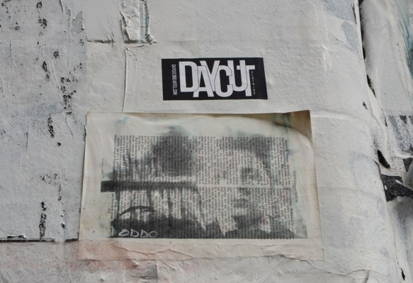 A stencil of a man's head on a page of an old book, pasted on an exterior wall.