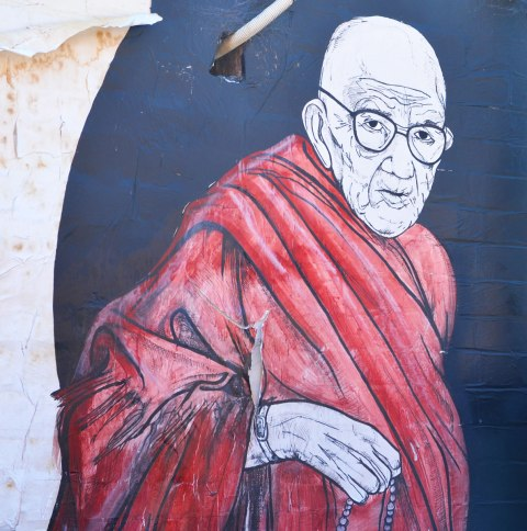a street art painting of an old bald man with glasses and reddish monk robes