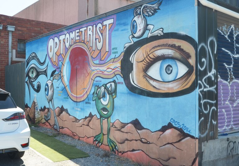 mural on the exterior wall of an optometrist's shop showing the parts of the eye in comic form.