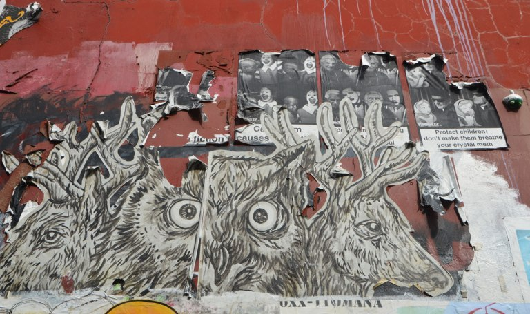a paste up of an owl and two deers that is starting to peel, it partially covers three poster pasteups that are even more frayed.