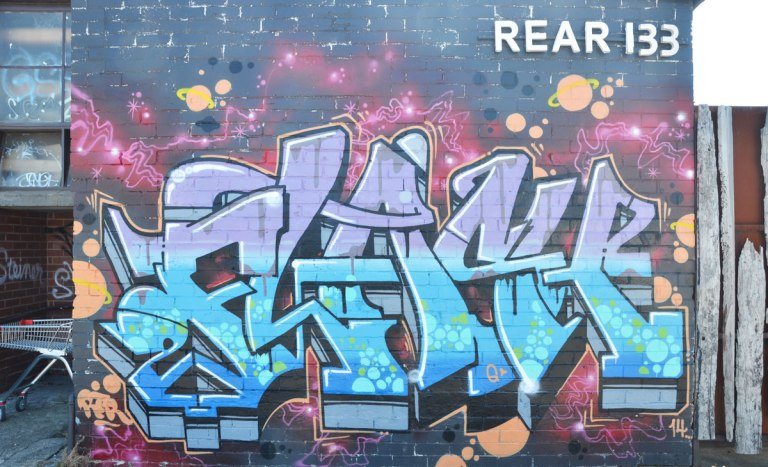 text street art on the rear of 133, purples and blues