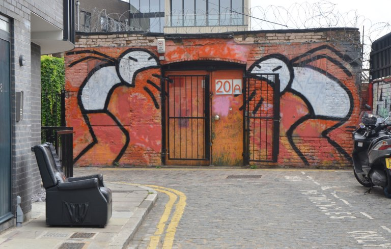 very large painting of two stick figures with white bodies, standing over the doorway of a building, and screaming at that doorway.