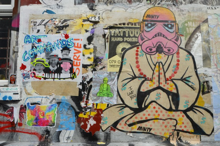 graffitii on a wall, a small green buddha, a large buddha with a storm strooper from Star Wars head by minty,