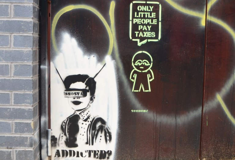 two pieces of street art, both stencils, First is a person with something in front of their face with the letters SSOSVA on it. The other is a surdude stencil of a little guy with the word bubble that says Only little people pay taxes.