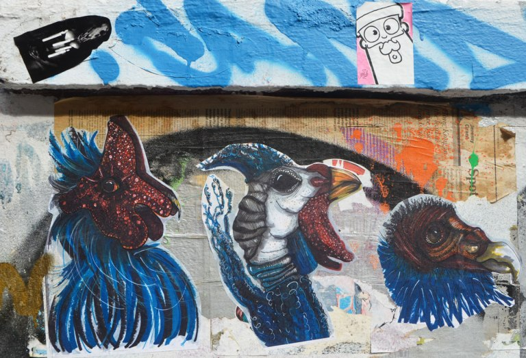 paste ups, three birds heads in blue, dark maroon and white,