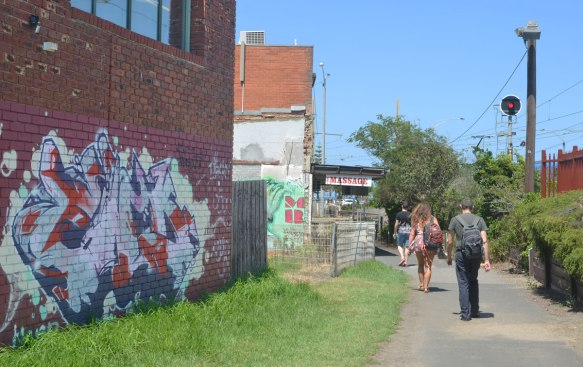 people wearing backpacks walking down a paved footpath past a building with street art on the side of it.