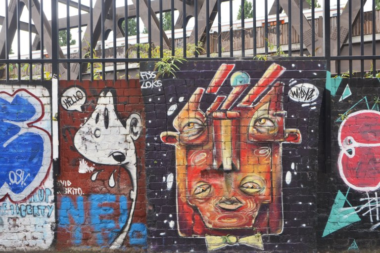 a street art painting of a head abstracted, squarish, with 4 eyes by widyz and another little white character saying hello beside it.