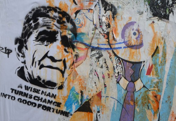 graffiti stencil of an older man's head with the words A wise man turns change into good fortune