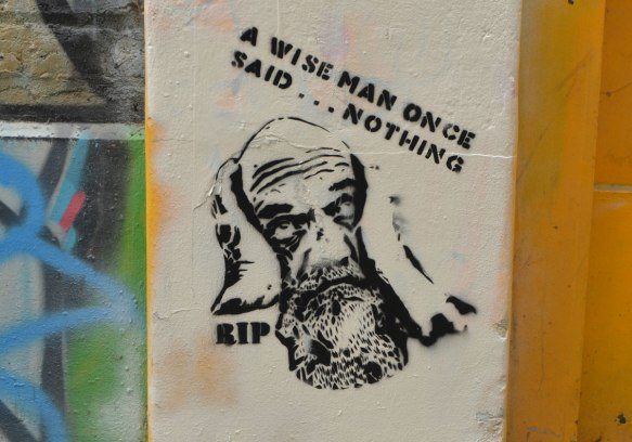 stencil of a bald man with a beard and one hand on his head, words that say A wise man once said nothing