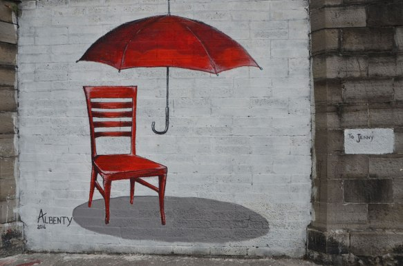 mural on a wll painted white, by Albenty and for Jenny, a red straight back wood chair with a red umbrella hovering above it