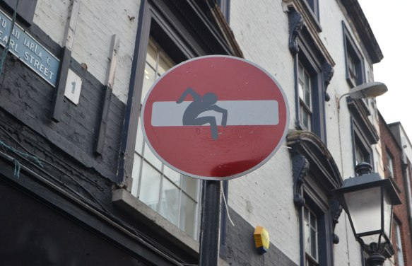 altered red and white circular no entry street sign, a black figure is trying to climb out of the white horizontal bar