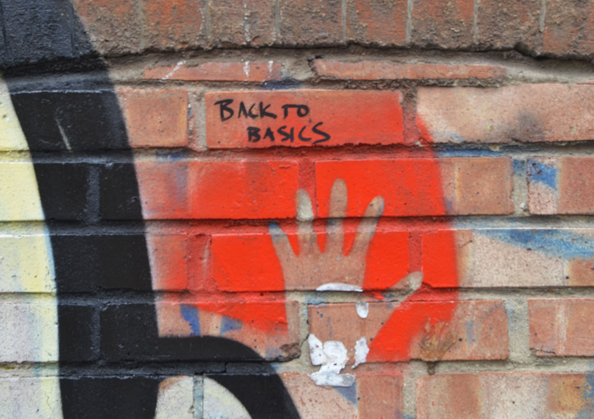 graffiti made of a handprint, hand on brick wall, spray with red, leave make of handprint. SOmeone has written, back to basics above the hand