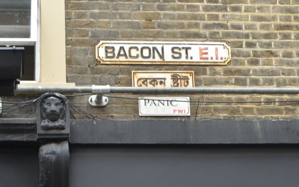 London street sign, Bacon St., E.1 with its Arabic counterpart below it. Also, a PANIC sign that is supposed to look like a street sign under that.