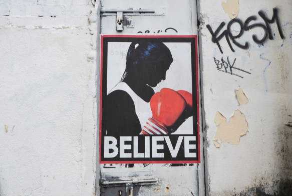 poster on a grubby dirty white wall of a woman in profile, black with white top and red boxing gloves held in front of her chest. The word believe is written in capital letters under her