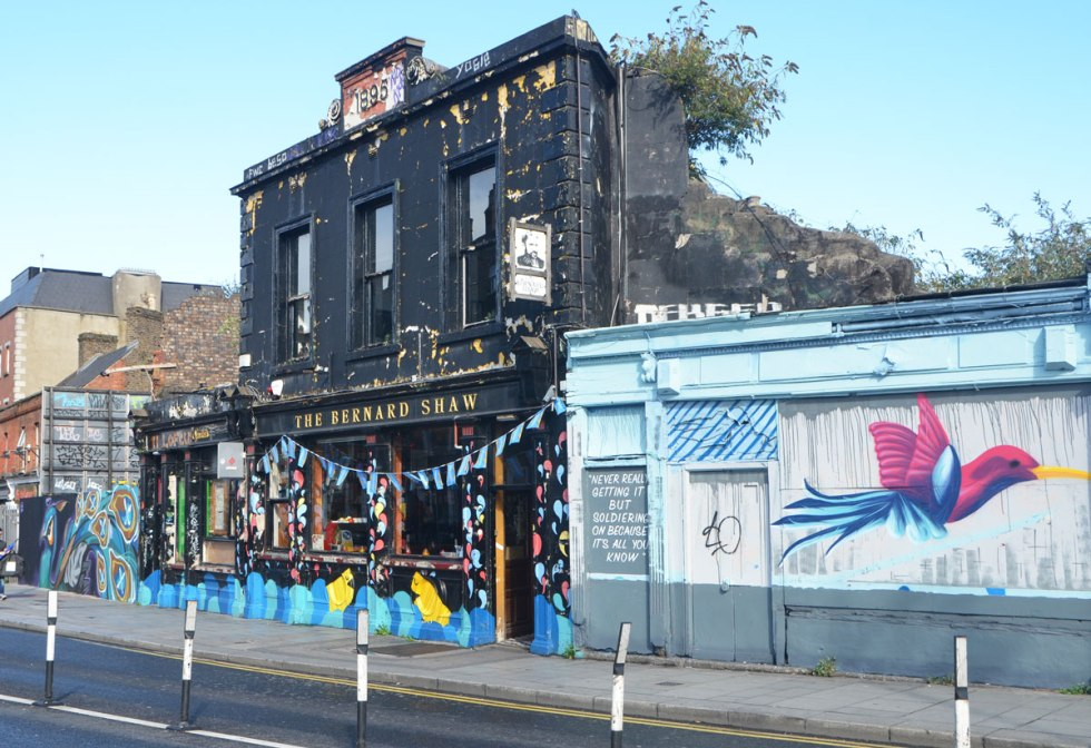 an old black building, the Bernard Shaw pub, built 1895, with street art on either side of it.