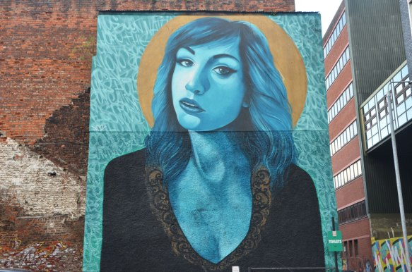 very large mural of a woman's upper body and head, done is shades of blue, shoulder length hair, looking at the viewer