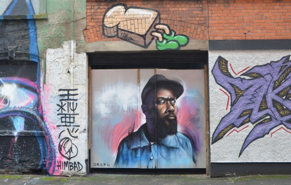 a street art painting of a slice of bread with green feet is above a street art painting by deph of a black man with a beard and a brown cap