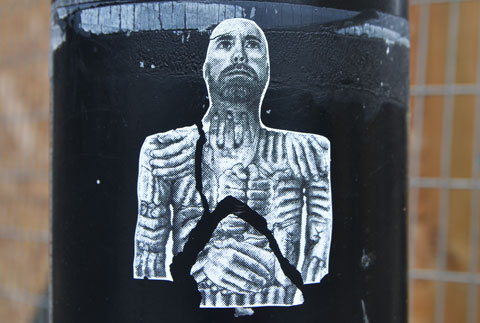 sticker on a black pole, torso and head of a man, looking upward, his body is covered with hands.