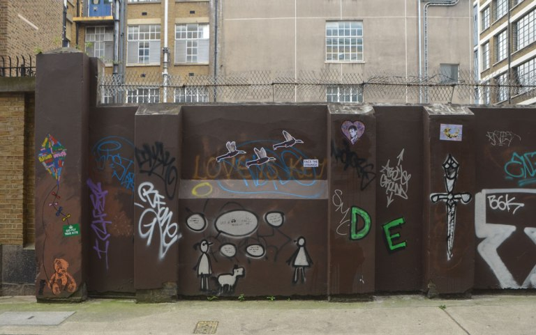 brown wall with barbed wire across the top, covered with graffiti