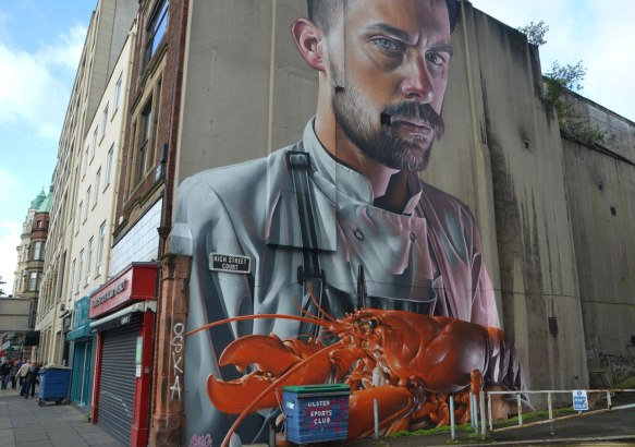 very marge mural of a man with moustache and small beard and wearing a chef's shirt is holding a large lobster