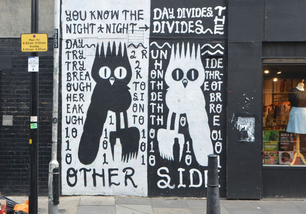 street art mural of two owls with text, one owl is black on white and the other is white on black. They are mirror images of each other. The text says You Know the day divides the night and night divides the day