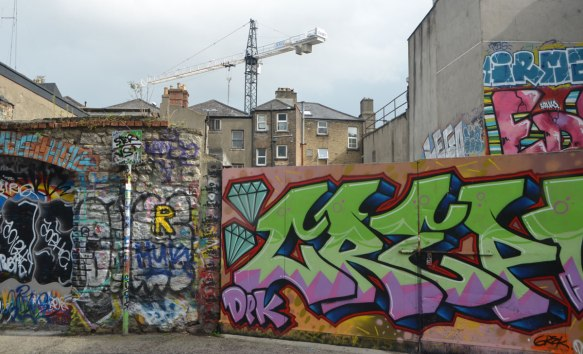 graffiti on a fence, with construction crane in the background