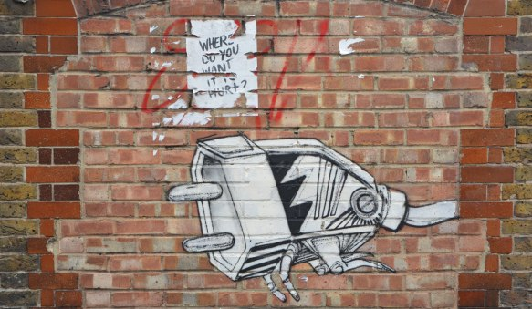 street art paste up of a drawing of an electric plug that has been made into a four legged creature.