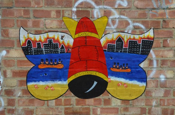 coloured paste up of bomb with wings and on the wings is painted a cityscape with river and people in lifeboats, life jackets washed up on the shore